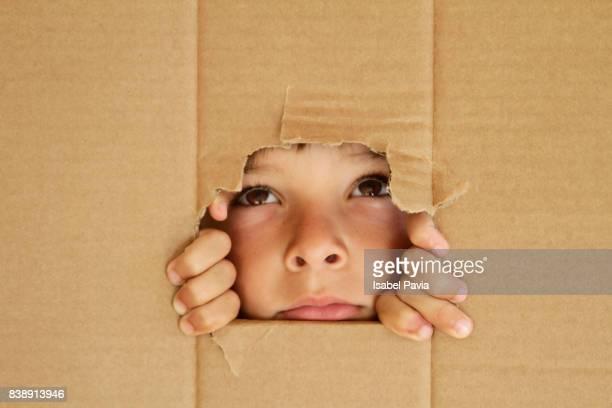 Boy looking through a hole on cardboard