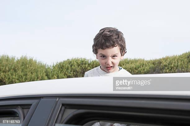 Boy looking through a sunroof of a car