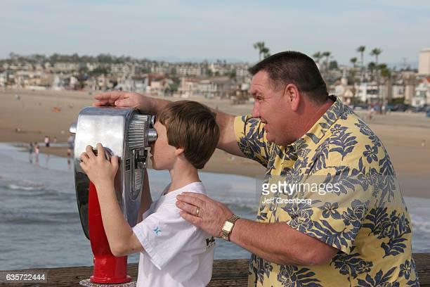 A boy looking through a telescope on the pier at Newport Beach