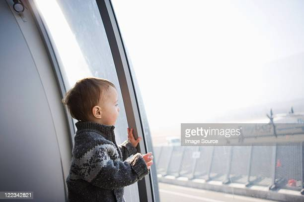 boy looking through airport window - toddler at airport stock pictures, royalty-free photos & images