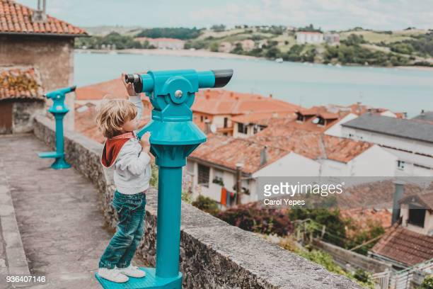 boy looking through binoculars at scenic view , cantabria,spain - pueblo fotografías e imágenes de stock
