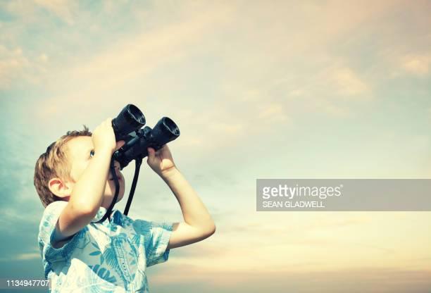 boy looking through binoculars at sky - binoculars stock pictures, royalty-free photos & images