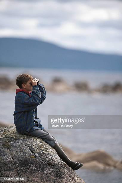 Boy (8-9) looking through binoculars