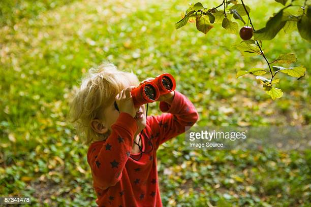 A boy looking through binoculars