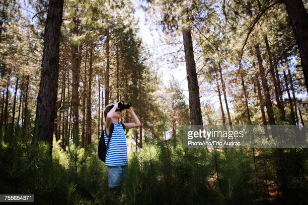 Boy looking through binoculars while hiking in woods