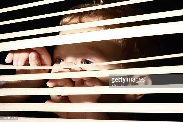 Boy looking through blinds