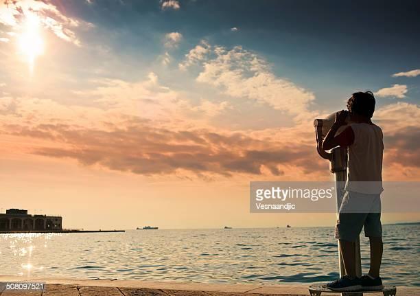 Boy looking through coin operated binoculars