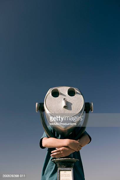 Boy (7-9) looking through coin operated viewer