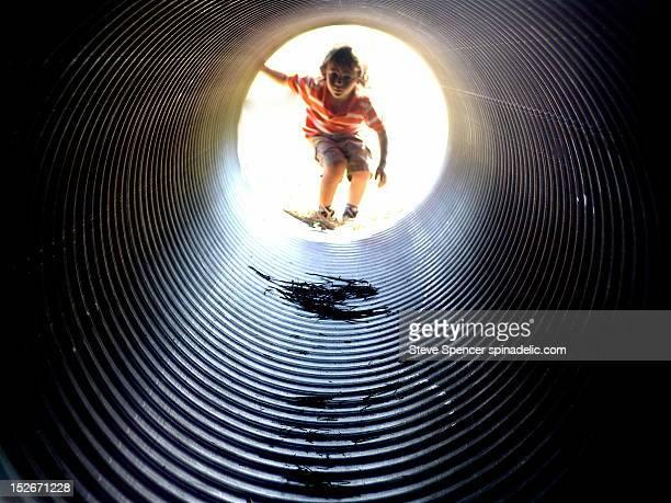 Boy looking through large tube