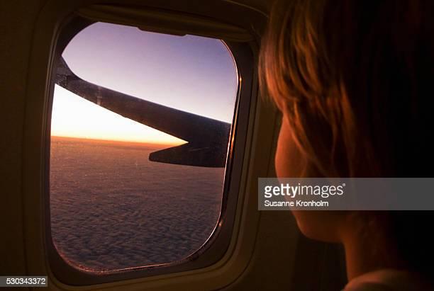 Boy looking through plane window