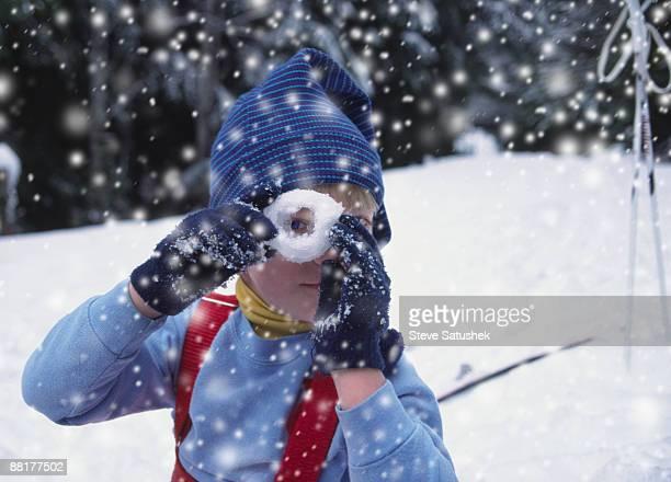 Boy looking through snow donut