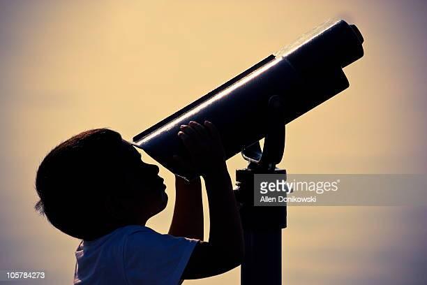 Boy looking through telescope at beach