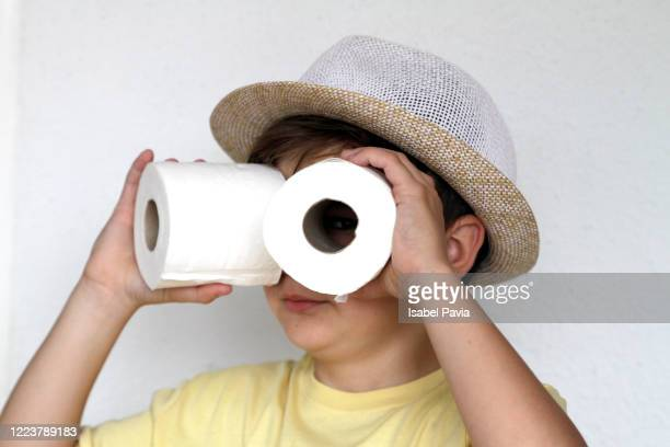boy looking through toilet paper rolls - funny toilet paper stock pictures, royalty-free photos & images