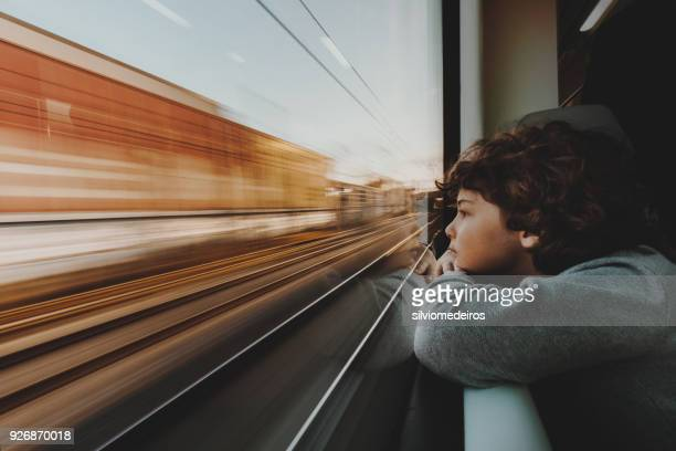 boy looking through train window - velocidad fotografías e imágenes de stock