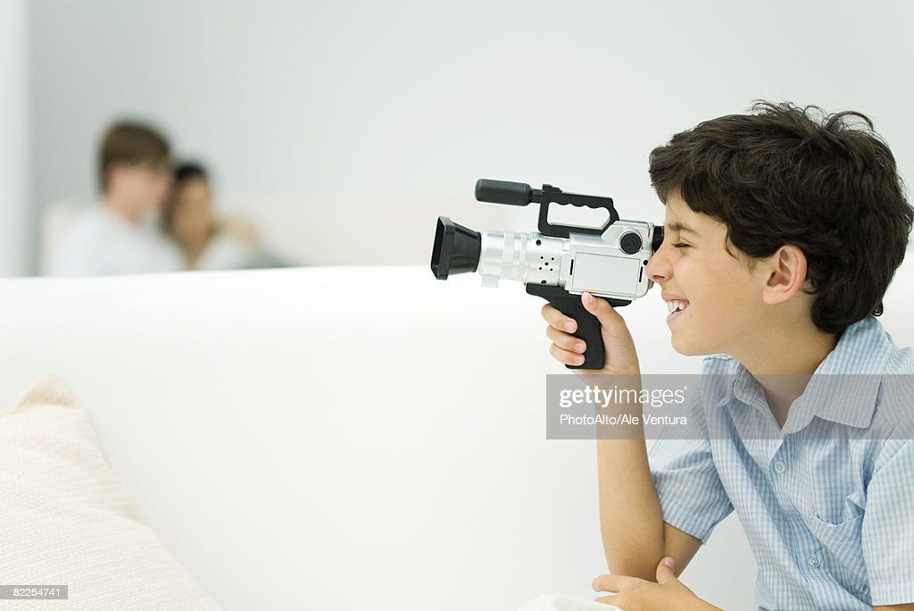 Boy looking through video camera, couple in background, side view : Stock Photo