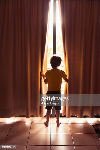 Boy looking through window at morning, Spain