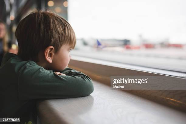 boy looking through window of restaurant - kid in airport stock pictures, royalty-free photos & images