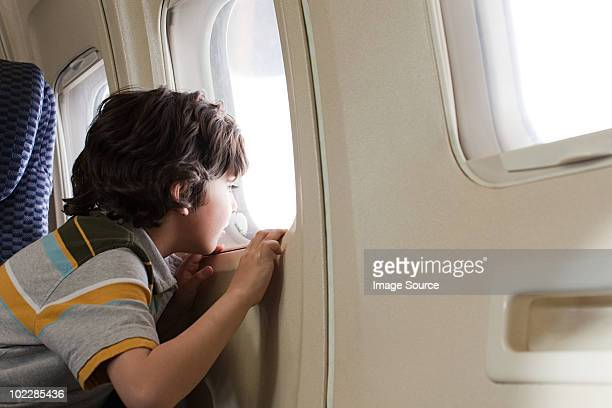 Boy looking through window on an airplane