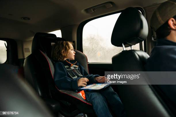 boy looking through window while sitting in car - family inside car stock photos and pictures