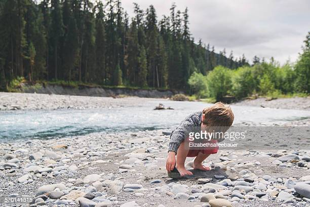 Boy looking under a rock in a river bed