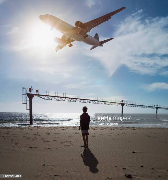 boy looking up at airplane flying low over ocean near lanzarote airport, puerto del carmen, spain - puerto del carmen stock pictures, royalty-free photos & images