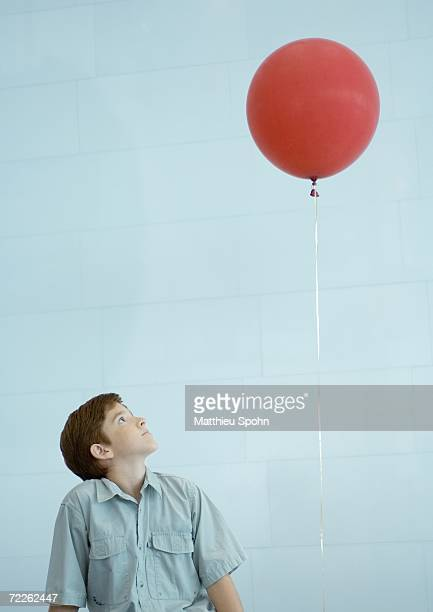 boy looking up at balloon - leggerezza foto e immagini stock