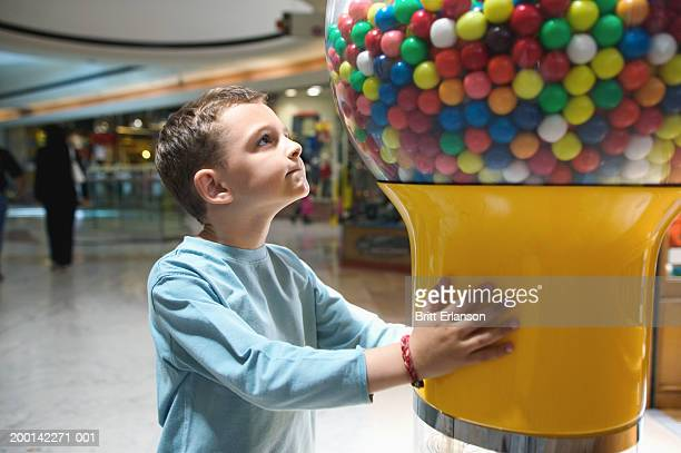 boy (4-6) looking up at gum ball machine in shopping mall - gumball machine stock pictures, royalty-free photos & images