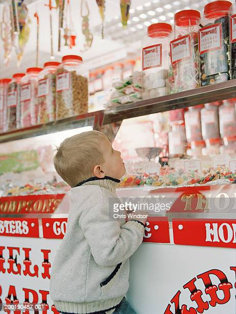 Boy (3-5) looking up at jars of sweets on shop counter