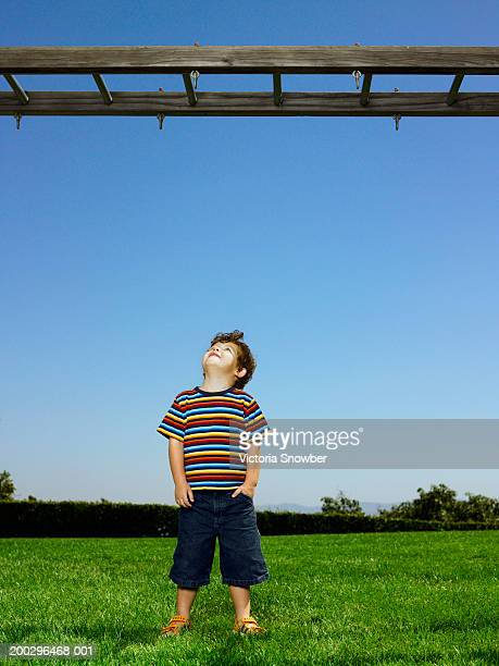 Boy (3-5) looking up at monkey bars
