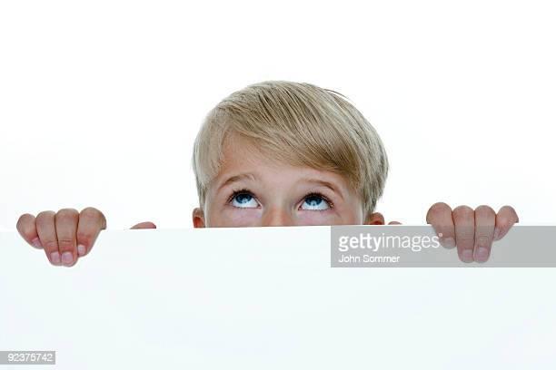 Junge, die sich hinter einer Mauer