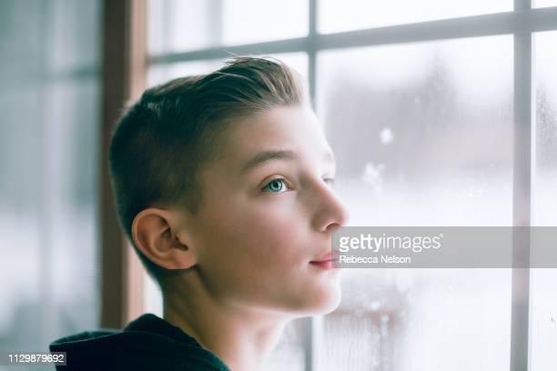 boy looking up illuminated by window light