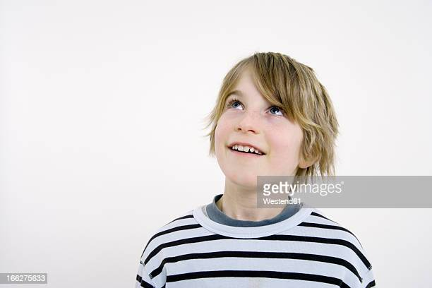Boy (10-11) looking up, white background