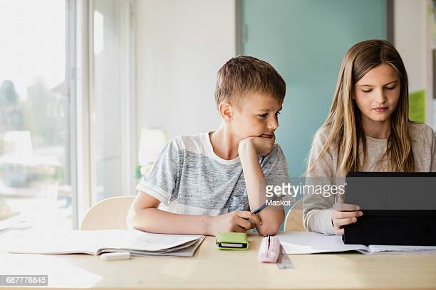 Boy looking while girl using tablet at desk in classroom