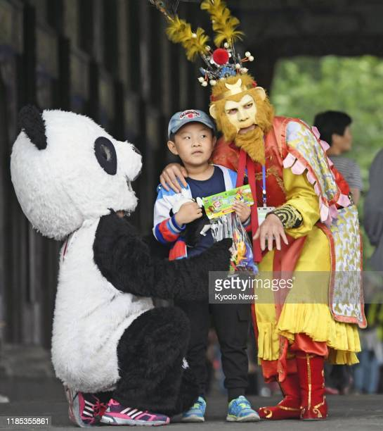 A boy looks a little intimidated by two mascots a sneakerwearing panda and one that looks like Monkey from the novel Journey to the West at a tourist...