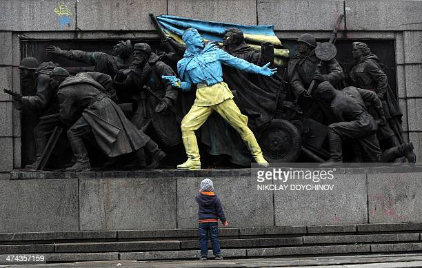 A boy looks at a figure painted in the colours of Ukraine on the monument of the Soviet Army in central Sofia on February 23 2014 The main Soviet...