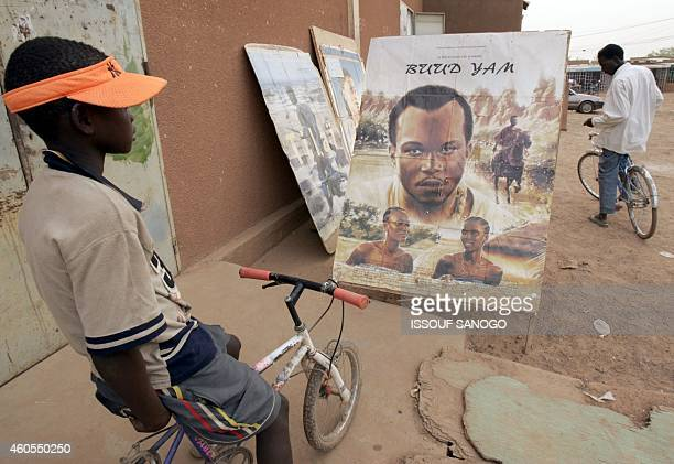 Boy looks at a film poster outside a cinema in Ouagadougou 02 March 2005 during the Ouagadougou Panafrican Festival of Cinema and Television . AFP...
