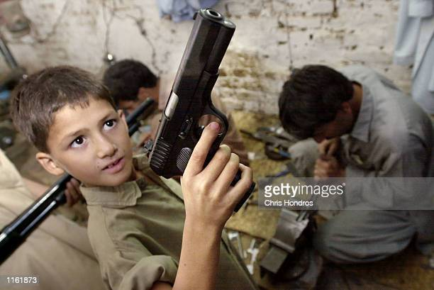 A boy looks at a newly refurbished gun while others work in a gun shop September 25 2001 in the village of Sagort in northern Pakistan Dozens of arms...