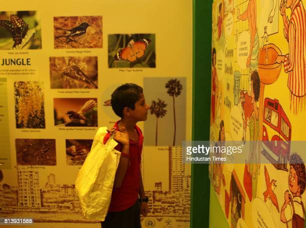 A boy looks at a photo exhibition of Mumbai Environment held on the occasion of World Environment Day at CST railway station