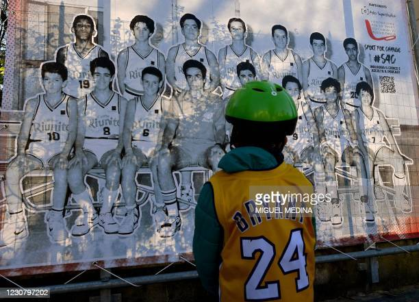 Boy looks at a photo exposition showing a boy Kobe and teammates during the inauguration ceremony of a square named after late Los Angeles Lakers...