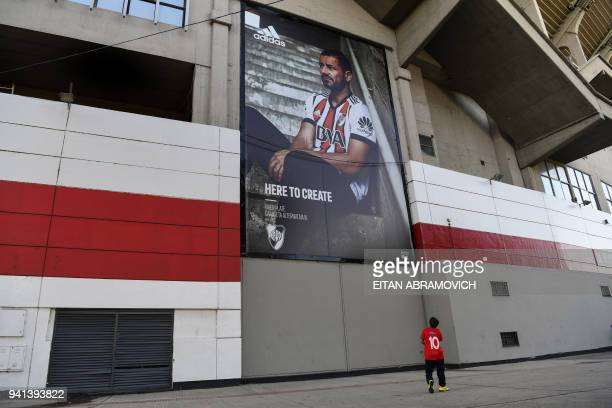 Boy looks at a picture of River Plate's forward Rodrigo Mora at an advertising sing hanged outside the club's stadium in Buenos Aires on April 3,...