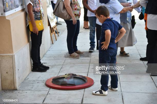 A boy looks at a quartz and bronze medal marking the place where late priest Pino Puglisi was murdered in 1993 as residents wait for the arrival of...