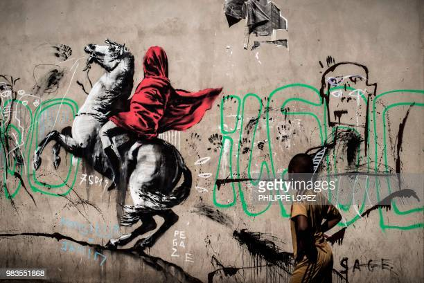 A boy looks at a recent artwork by street artist Banksy in Paris on June 25 2018 Anonymous street artist Banksy's artwork of Napoleon Bonaparte...