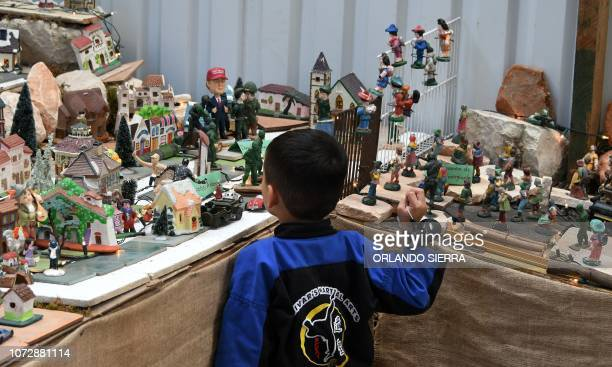 TOPSHOT A boy looks at a representation of the Central American migrant caravan of mostly Honduras that has angered US President Donald Trump which...