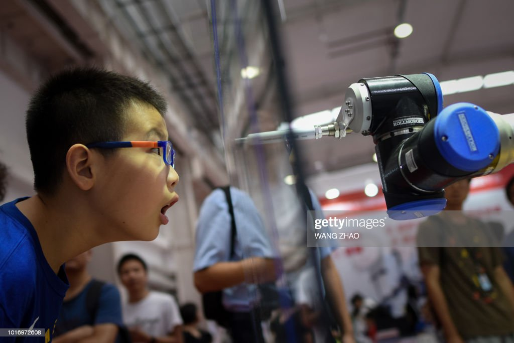 A boy looks at a robot arm at the 2018 World Robot Conference in Beijing on August 15, 2018.