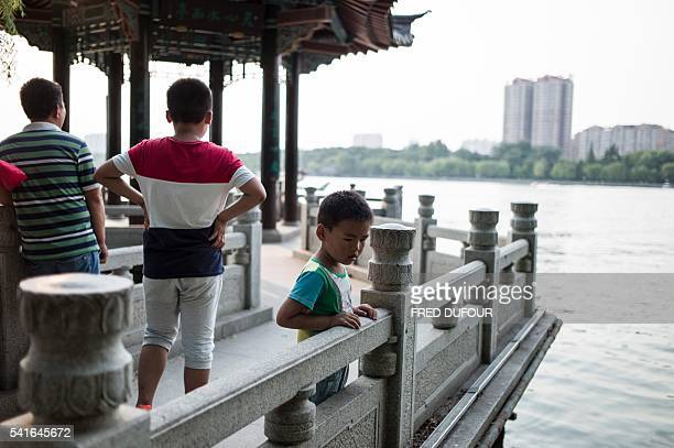 A boy looks at fishes in Daming Lake in Jinan Shandong province on June 18 2016 Jinan is also called the 'Spring City' for its wellknown water...