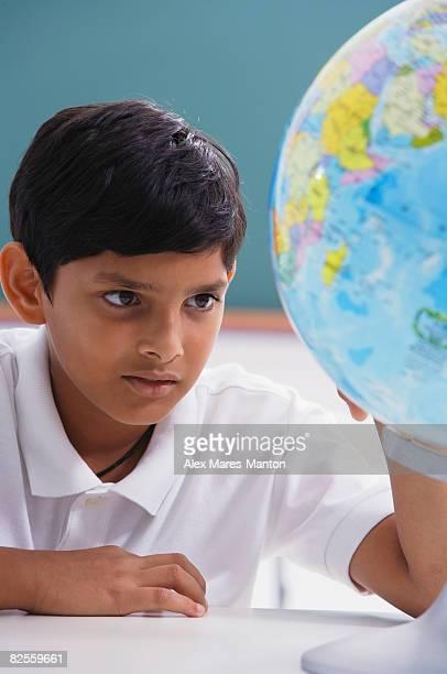 boy looks at globe, one hand on globe