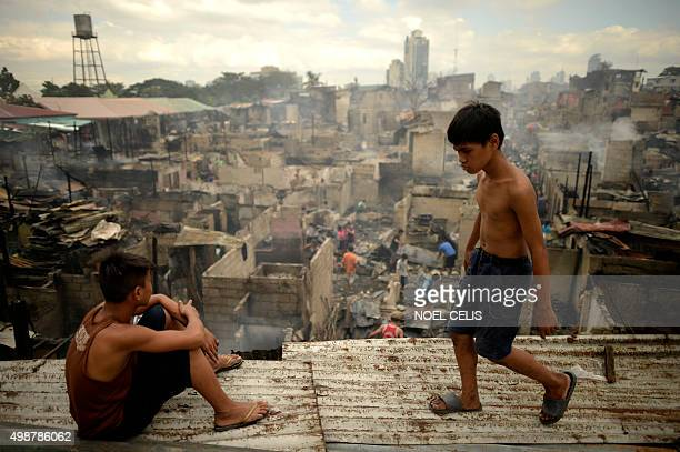 A boy looks at houses destroyed by a huge fire in a slum area in Mandaluyong City suburban Manila on November 26 2015 A huge fire that swept through...