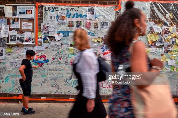 A boy looks at messages left by wellwishers in tribute to the victims of the June 14 Grenfell Tower block fire near the scene of the fire in North...
