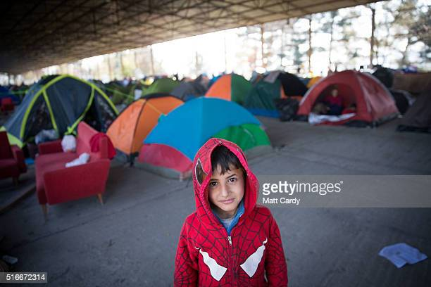 A boy looks at the camera as he stands in front of tents erected inside an old railway shed where people are sheltering at the Idomeni refugee camp...