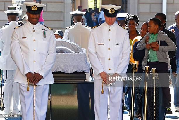 A boy looks at the coffin of South African former president Nelson Mandela as people bid farewell to Mandela as hes lie in state at the Union...